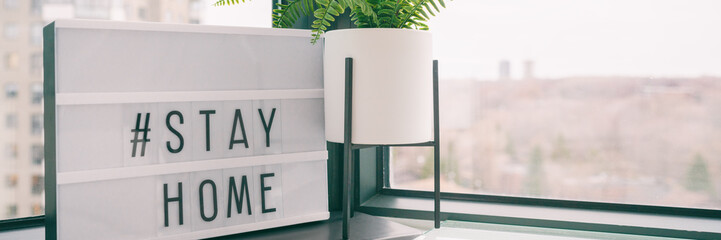 COVID-19 banner Coronavirus staying at home lightbox message sign with text hashtag #STAYHOME glowing in light to promote self isolation staying at home header background. Fototapete