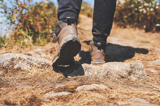 Closeup image of a woman hiking with trekking boots on the top of mountain