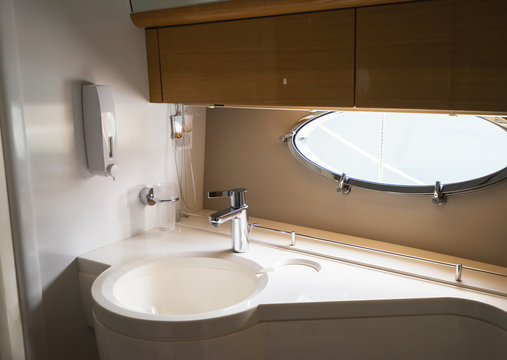 Sink and silver faucet in the luxury yacht. Selective focus.