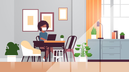 african american woman in protective mask using laptop coronavirus pandemic quarantine concept work from home online education freelance modern living room interior full length horizontal vector Wall mural