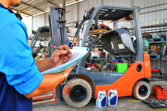 The mechanic is checking the quality and Maintenance Forklift,Energy fuel concept.