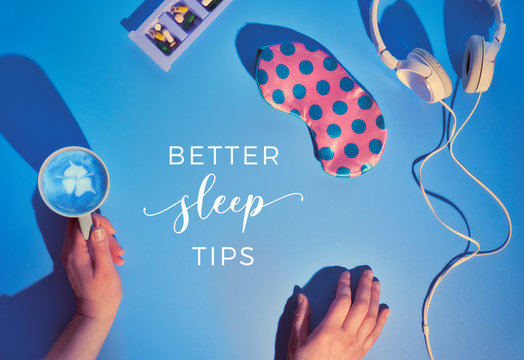 "Text ""Better sleep tips"". Healthy night sleep creative concept. Sleep mask in pastel colors, earphones, calming pills to help insomnia, sleep log notebook. Blue mint background, long shadow design."
