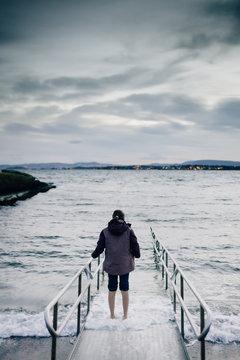 Teenager alleine am Ufer nach Beschränkungen wegen Corona Krise im März 2020 MR yes