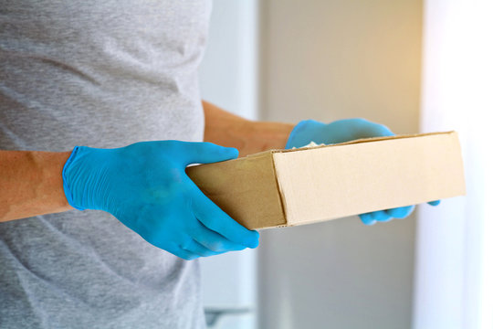 Closeup male hands in blue rubber gloves hold cardboard boxes.