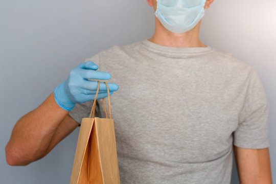 A man in a medical mask and blue rubber gloves holds a paper bag in his hands. Safe shopping concept.