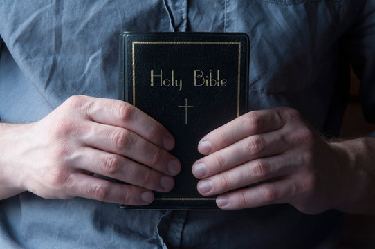 The Bible is in the hands. Bible on the chest. Priest man