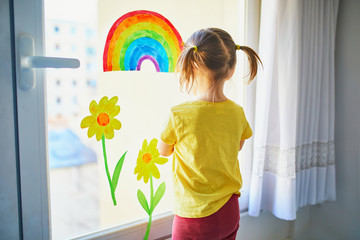 Adorable toddler girl attaching drawing of rainbow to window glass as sign of hope Fotomurales