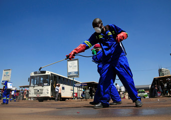 City health workers spray disinfectant at a bus terminus during a 21 day nationwide lockdown to limit the spread of coronavirus disease (COVID-19) in Harare