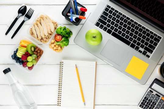 Take away nutrient rich food with laptop computer and equipment on the table prepared for working from home