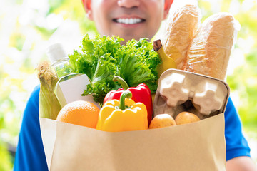 Smiling delivery man holding a grocery bag ready to deliver to the customer at home Wall mural