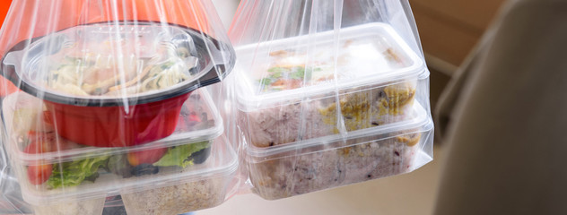 Panoramic banner image of Asian food boxes in plastic bags delivered to customer at home by delivery man