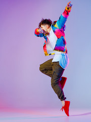 Guy dancing contemporary dance in studio. Neon light grey background. Acrobatic bboy dancer. Break dance lessons.