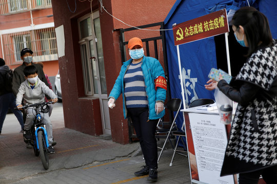 A community volunteer wearing a face mask holds a thermometer next to a tent for temperature checks and registration at an entrance of a residential compound, as the country is hit by an outbreak of the novel coronavirus disease (COVID-19), in Beijing