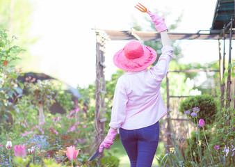 Happy woman in the garden, flowers around