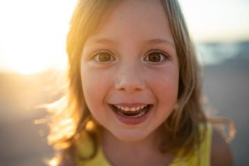 Portrait shot of cheerful little girl during sunset Fototapete