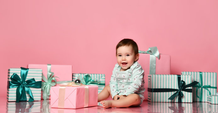 baby girl sitting on the floor with gift box