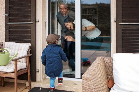 Quarantine, self isolation and social distancing during coronavirus pandemic. Old senior grandparents couple communicate to grandson through closed window. Lockdown