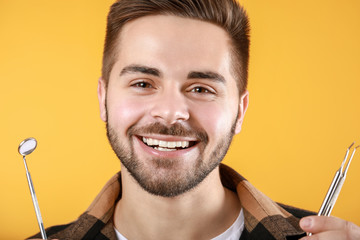 Fotomurales - Happy smiling young man with dentist's tools on color background
