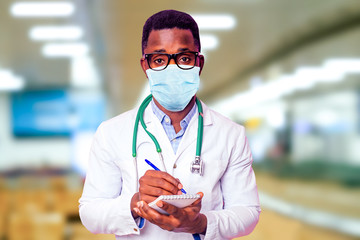 happy male african medical surgeon infectious disease specialist doctor in a white coat on a background hospital lights .epidemic corona virus prevention