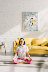 Girl with colorful hair and closed eyes meditating on yoga mat in living room