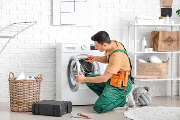 Obraz Worker repairing washing machine in laundry room - fototapety do salonu