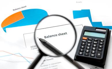 Balance sheet. Filling out the documents. Balance sheet form, graphs, magnifier, calculator