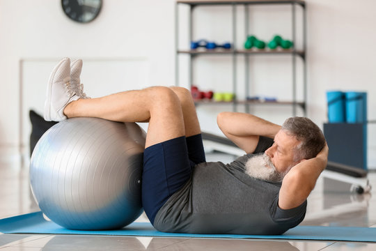 Sporty elderly man training in gym