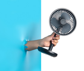 Hand holding Electric table fan through the torn blue plastic isolated on white background