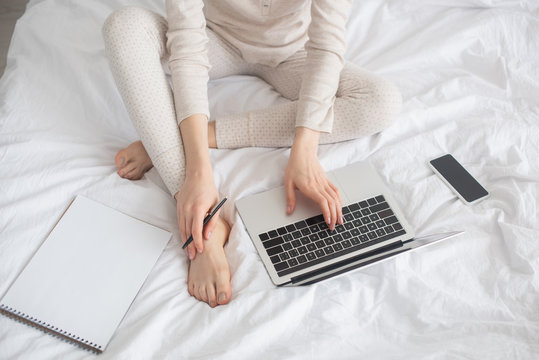 Partial view of freelancer with pen working on laptop near smartphone and notebook on bed