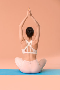 Young woman practicing yoga on color background