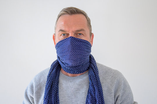 Bust portrait of man in blue scarf over his face