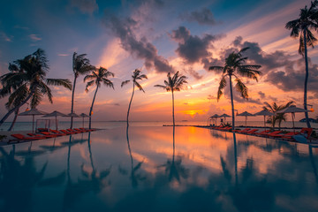 Wall Mural - Beautiful poolside and sunset sky with palm trees silhouette. Luxurious tropical beach landscape, deck chairs and loungers and water reflection. Tranquil summer vacation, travel concept infinity pool