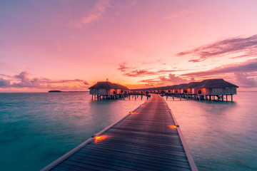 Wall Murals Candy pink Amazing sunset landscape. Picturesque summer sunset in Maldives. Luxury resort villas seascape with soft led lights under colorful sky. Dream sunset over tropical sea, fantastic nature scenery