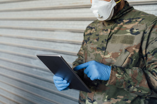 Military detail with mask and gloves using a portable tablet. Pandemic crisis, Spanish soldier.