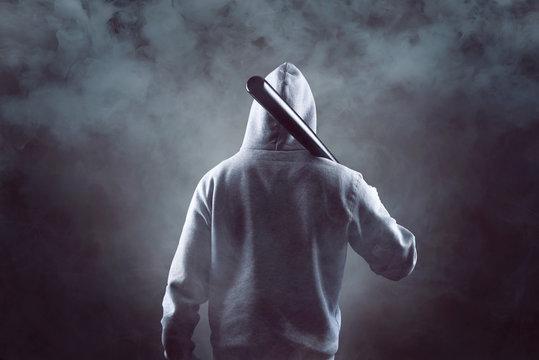 Mann mit Kapuzenpullover und Baseballschläger in der Dunkelheit