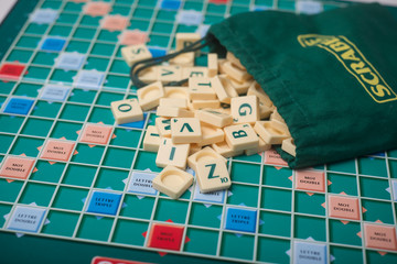 Mulhouse - France - 1 April 2020 - Closeup of plastic letters of Scrabble game fallen from bag on boardgame