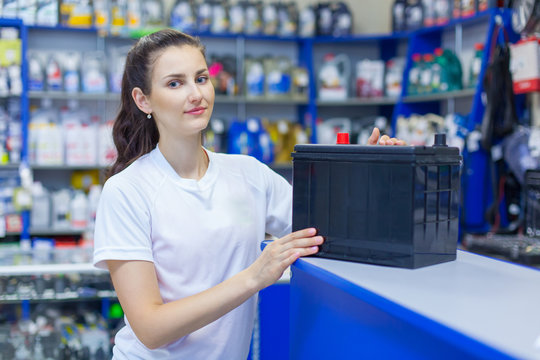 Beautiful girl saleswoman offers the best battery for car in an auto parts store