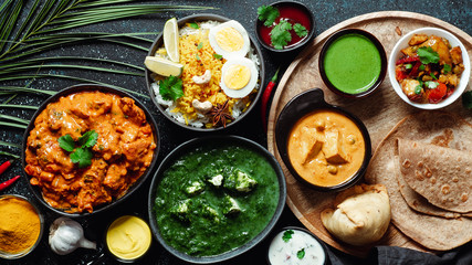 Indian cuisine dishes: tikka masala, paneer, samosa, chapati, chutney, spices. Indian food on dark background. Assortment indian meal top view or flat lay. Copy space for text. Fotomurales
