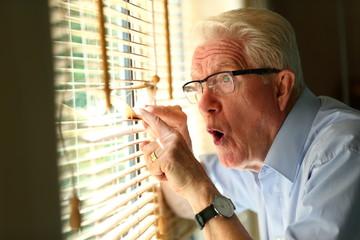 Curious elderly man peeking through the blinds by the window