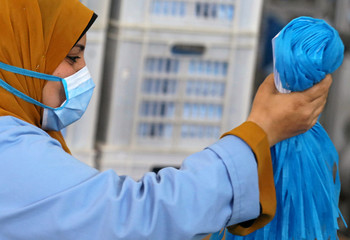 A woman wearing a protective face mask works in a factory that produces sterilised surgical equipment and medical clothings in Egypt