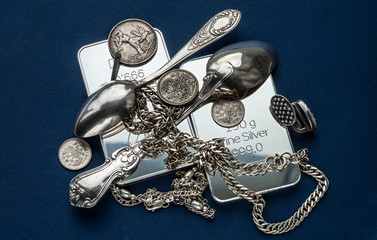 Silver bullion, silverware, jewelry and old coins on a dark blue background.