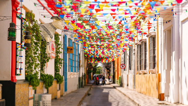 Beautiful and colorful colombian street with pennant flags decorating the houses, big statue in the shape of a cow wearing a typical Colombian hat. Colorful abundant fair flags on beautiful day.