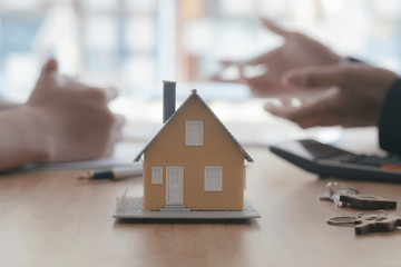 Close up house model on blur background of real estate agent and customer