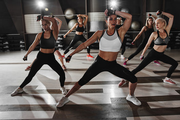 Women in black and white sportswear on a real group body Combat workout in the gym train to fight,...
