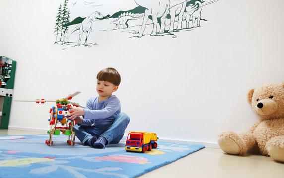 Ein vierjähriger Junge spielt allein in seinem Kinderzimmer am 03.03.20.