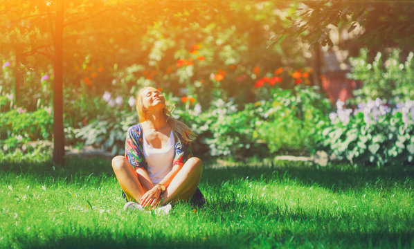 Happy free young woman sitting outdoors in yoga position with closed eyes on summer park grass Calm girl enjoy smile and relax in spring city air. Mindset inner light peace concept. Bali asia sun joy