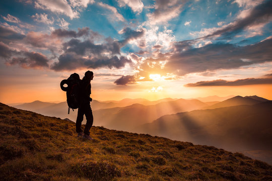 Hiking trough epic mountain landscape with a big backpack, exploring and feeling the freedom of nature