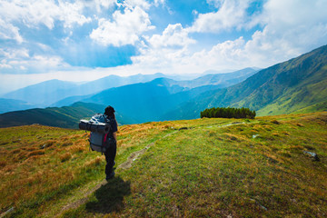 Hiking trough epic mountain landscape with a big backpack, exploring and feeling the freedom of nature Fotomurales