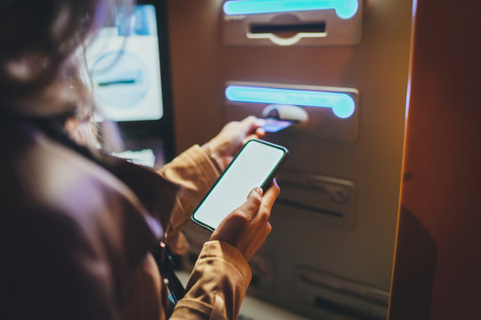 Woman using street ATM machine to withdraw money inserting a credit card while standing on street at night, young lady inserting her bank card into ATM machine to replenish account using smartphone