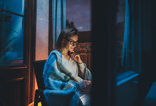 Home Office, Young businesswoman working remotely during quarantine from home late at night using laptop computer, Young woman entrepreneur in eyeglasses using portable computer sending monthly report